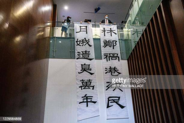 Banners reading 'Carrie Lam, the scourge of Hong Kong and its people' and 'Carrie Lam, leaves a stink for ten thousand years' are displayed by...
