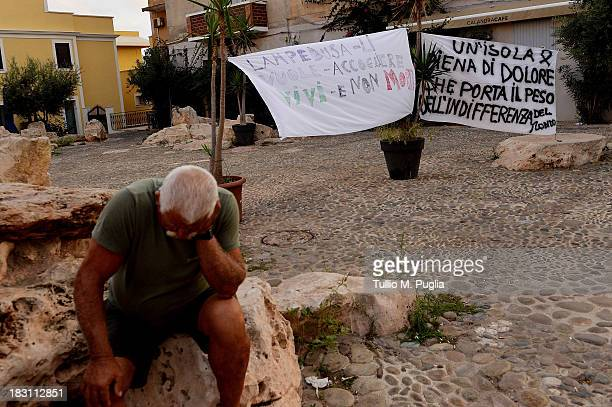 Banners reading 'Lampedusa wants to welcome them alive and not dead' and 'an island full of pain carries the weight of indifference' are displayed...