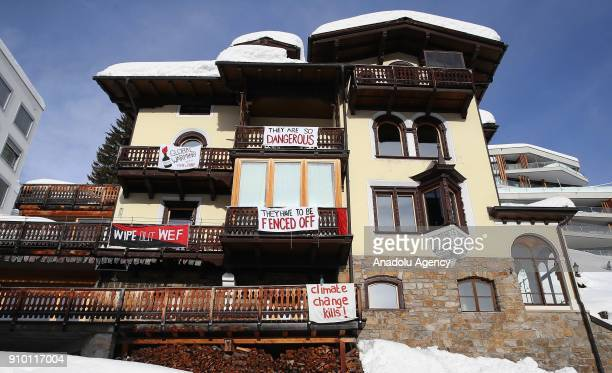 Banners reading 'They Are So Dangerous They Have To Be Fenced Off Climate Change Kills Wipe Out WEF Global Warming With Fire Fury' hang from a house...