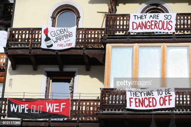 Banners reading 'They Are So Dangerous They Have To Be Fenced Off Wipe Out WEF Global Warming With Fire Fury' hang from a house while US President...