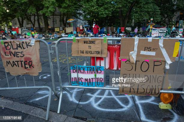 Banners seen as hundreds of protesters occupy the space around City Hall, awaiting details on how Mayor Bill de Blasio proposes to cut the budget of...