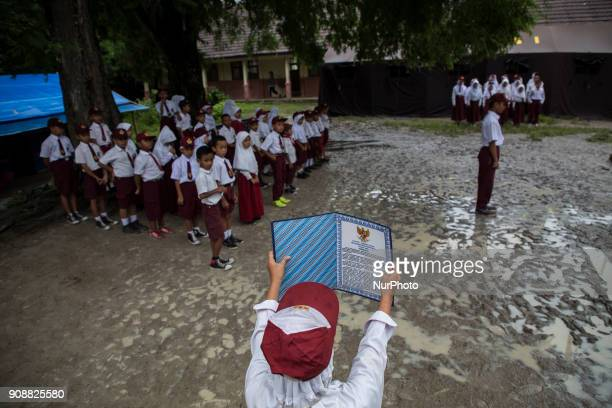 Regular morning monday ceremony before the class begin a student read the Indonesian basic law with very muddy field at the school Primary School...