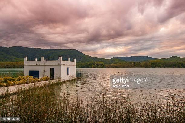 Banyoles lake with fisherman house pier at sunset