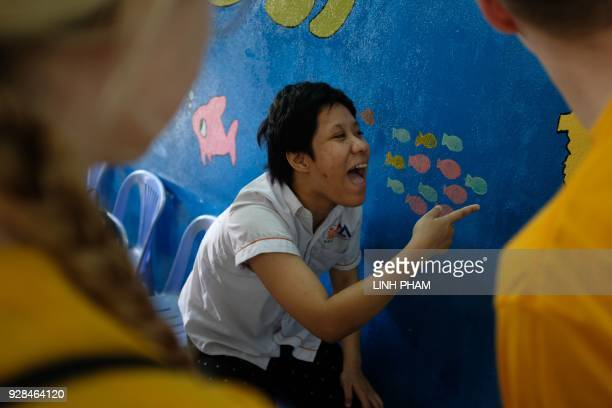 Bao Anh who suffers the affects of Agent Orange gestures to details on a mural as she interacts with crewmembers of the USS Carl Vinson at a centre...