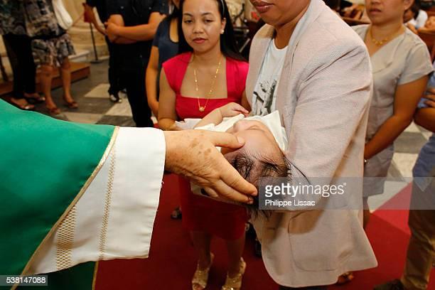baptism in a catholic church - catholic baptism stock pictures, royalty-free photos & images