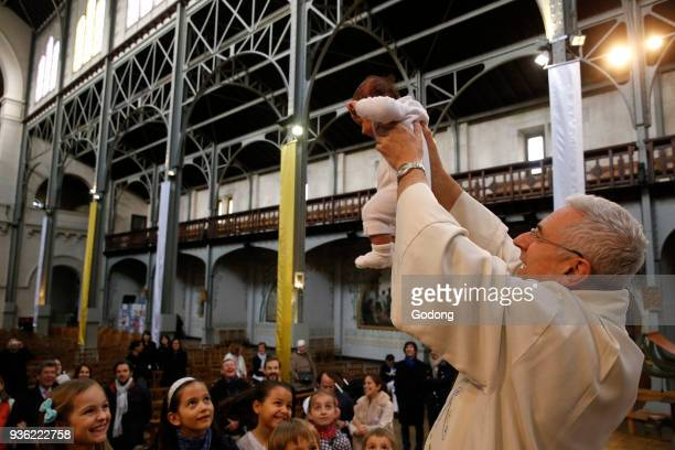 Baptism in a catholic church. Priest raising a baptised child. France.