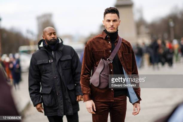 Baptiste Giabiconi wears a brown jacket, a burgundy leather crossbody Saddle Dior bag, outside Dior, during Paris Fashion Week - Womenswear...
