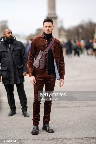 Baptiste Giabiconi wears a brown jacket, a burgundy leather crossbody Saddle Dior bag, brown pants, leather shoes, outside Dior, during Paris Fashion...