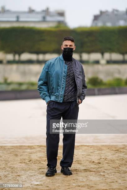 Baptiste Giabiconi wears a face mask a blue and gray bomber jacket a Dior monogram pullover black pants sneakers outside Dior during Paris Fashion...