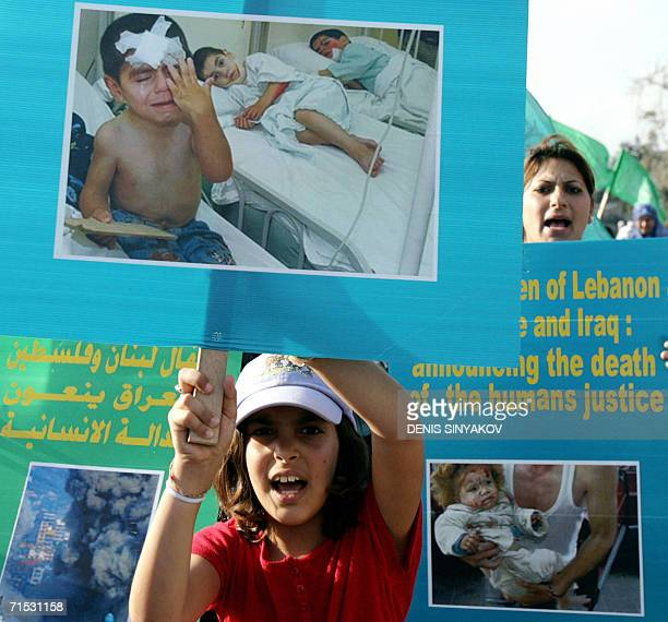 An ArabIsraeli girl holds up a picture of injured Lebanese children during a rally to condemn the Israeli offensive in Lebanon 28 July 2006 in the...