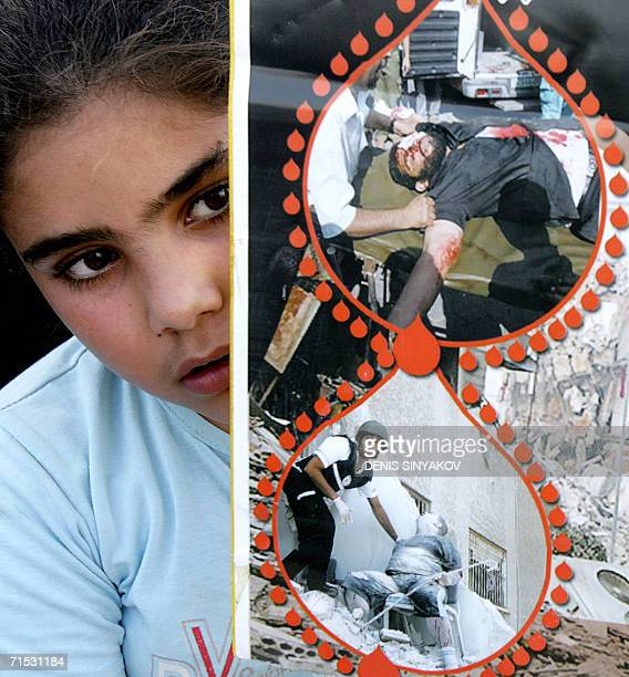 An ArabIsraeli girl holds up a picture of killed Lebanese and Palestinian people during a rally to condemn the Israeli offensive in Lebanon 28 July...