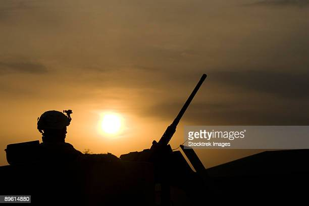baqubah, iraq - a us soldier mans his .50 caliber while waiting to move out on a mission at sunset. - baqubah fotografías e imágenes de stock