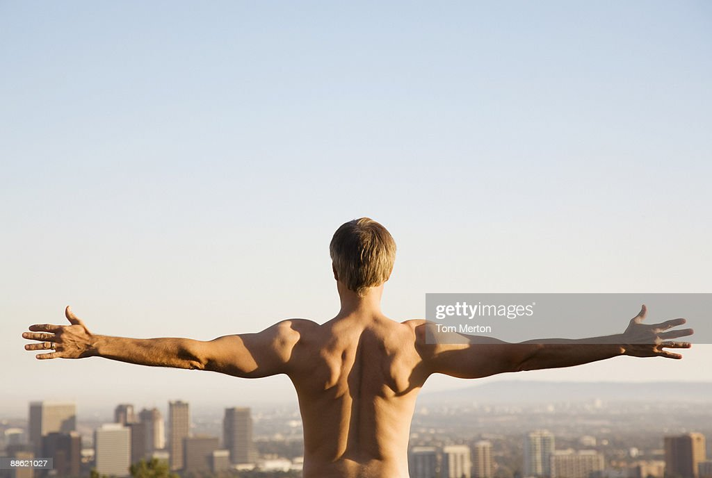 Bar chested man stretching on balcony overlooking city : Stock Photo