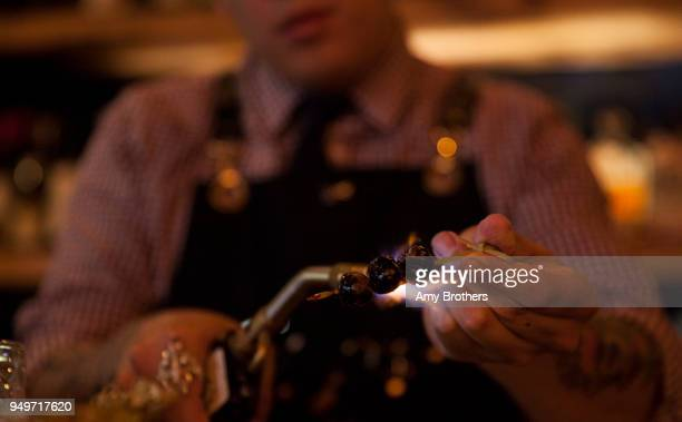 Bar manger TJ Vong caramelizes cherries with a blow torch for a 'The Enchanted' cocktail cocktail garnish at Mizu Izakaya on April 20 2018 in Denver...