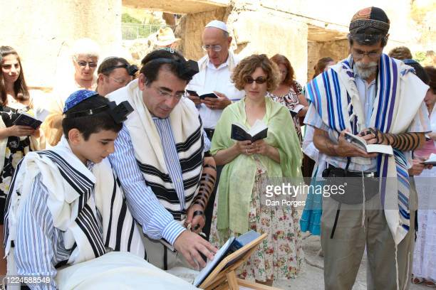 Bar Mitzva, a ceremony on a 13th birthday marking manhood for a Jewish boy, the boy reads from the Siddur with his father, mother and the Rabbi, men...