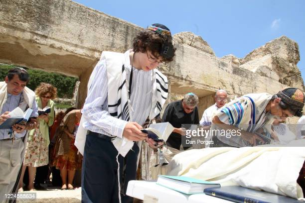 Bar Mitzva a ceremony on a 13th birthday marking manhood for a Jewish boy the boy's brother father Rabbi and relatives bend forward towards the...
