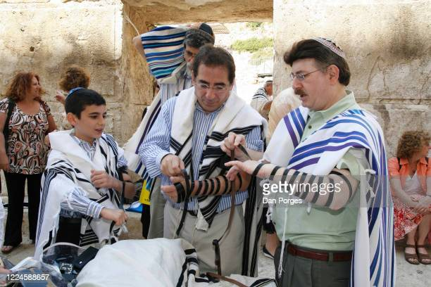 Bar Mitzva a ceremony on a 13th birthday marking manhood for a Jewish boy the boy learns from his father standing in front of him how to put on the...