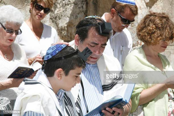 Bar Mitzva a ceremony on a 13th birthday marking manhood for a Jewish boy the boy's father holds his hand on his son's head and blesses him while he...