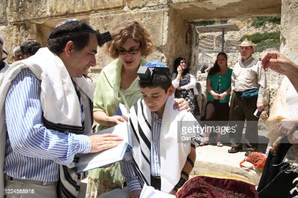 Bar Mitzva, a ceremony on a 13th birthday marking manhood for a Jewish boy, the boy is being blessed by his father who holds a Siddur and mother,...