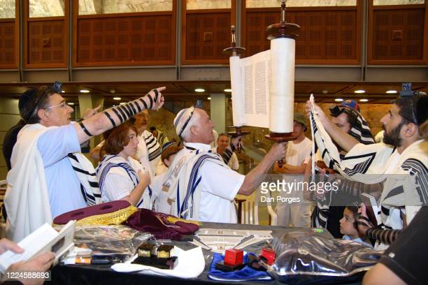 Bar Mitzvah, the ceremony which marks manhood for a Jewish boy, 13 years old, taking place at a Western or Wailing Wall, the boy and the other men...