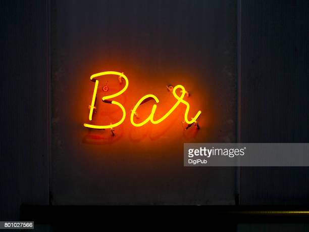 'Bar' neon sign on the wall in the night