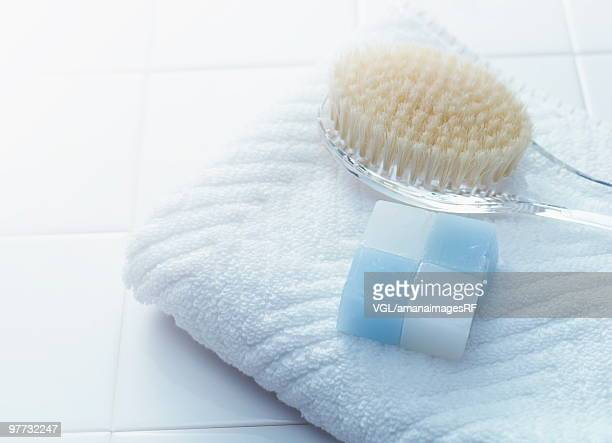 Bar of soap, back brush and towel in the bathroom