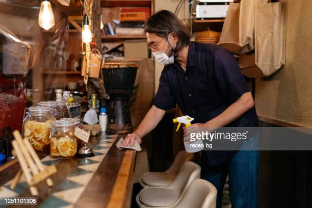 bar owner disinfecting bar counter surface to clean illness bacteria - catering building stock pictures, royalty-free photos & images