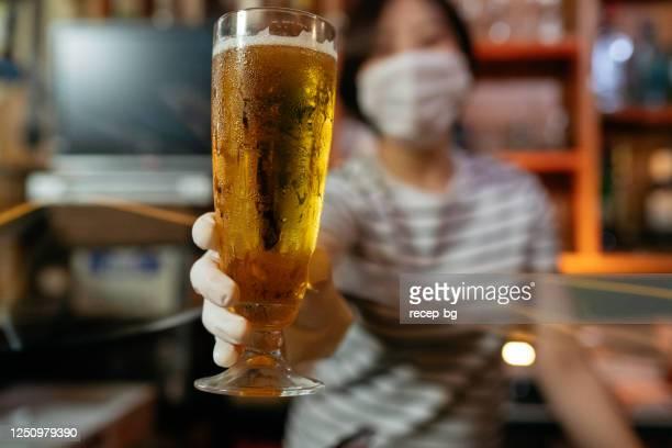 barbesitzer serviert bier mit schützendem plastikhandschuh hinter schützendem kunststoffvorhang - corona beer stock-fotos und bilder