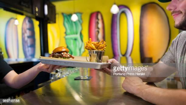 Bar server Maya Doyle serves Garrett Jones of Portland a bacon burger with bbq sauce feta cheese and at the Brown Street Portland establishment