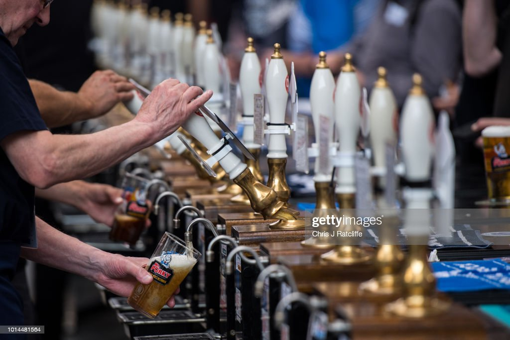 Bar staff serve beer during the Great British Beer Festival at Olympia Exhibition Centre on August 10, 2018 in London, England. The five day festival showcases over 900 real ales and craft beer and is organised by Campaign for Real Ale group CAMRA.