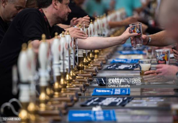 Bar staff serve beer during the Great British Beer Festival at Olympia Exhibition Centre on August 10 2018 in London England The five day festival...