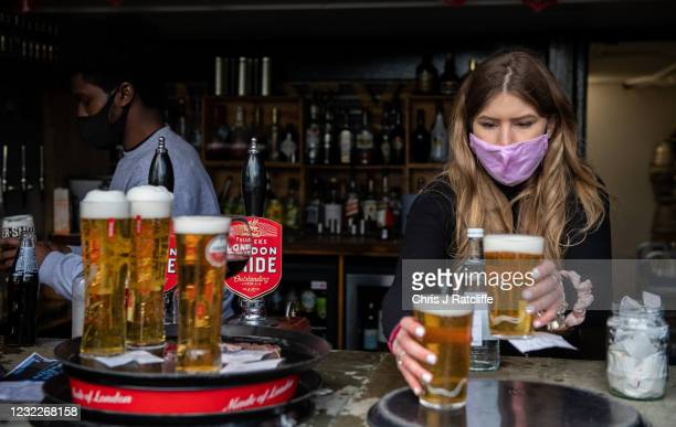 Bar staff serve beer for table service in the garden of the The Duke of Kent pub which reopened at lunchtime today on April 12, 2021 in London,...