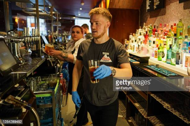 Bar staff serve drinks on the first day of pubs reopening at the Job Bulman pub in Gosforth on July 04, 2020 in Newcastle upon Tyne, England. The UK...