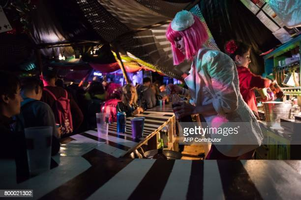 Bar staff serve festivalgoers in the Rabbit Hole bar in 'The Park' area of the Glastonbury Festival of Music and Performing Arts on Worthy Farm near...