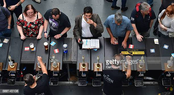 Bar staff serve visitors at the CAMRA Great British Beer festival at Olympia London exhibition centre on August 10, 2016 in London, England. The five...