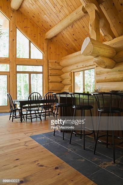 bar stools at breakfast bar on tiled floor in eastern white pine log cabin with vaulted ceiling - eastern white pine stock pictures, royalty-free photos & images