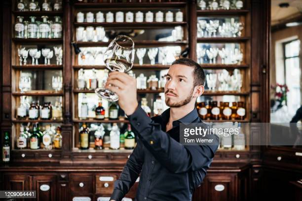 bar tender checking wine glass for dust - zwart shirt stockfoto's en -beelden