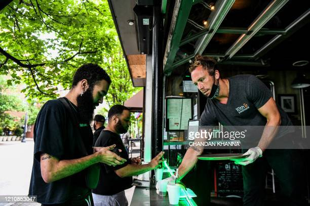 Bar tender Jake Glazier serves his customers at an open roadside bar in Atlanta, Georgia, on April 23, 2020. - The US state of Georgia takes a...