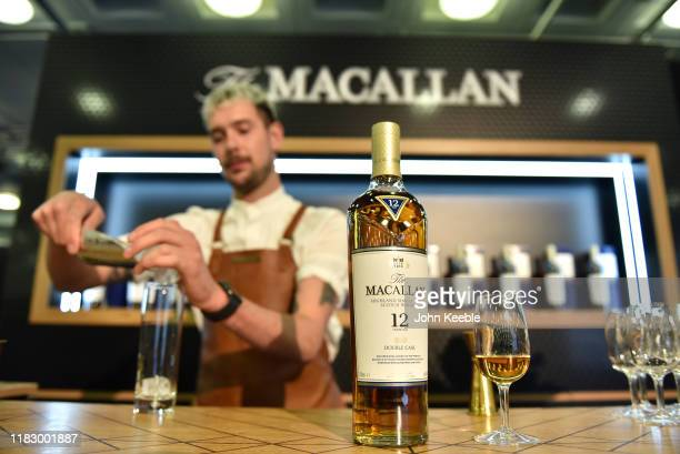 Bar tender pours 12 years old Macallan highland single malt scotch whisky during the RM Sotherb's London, European car collectors event at Olympia...