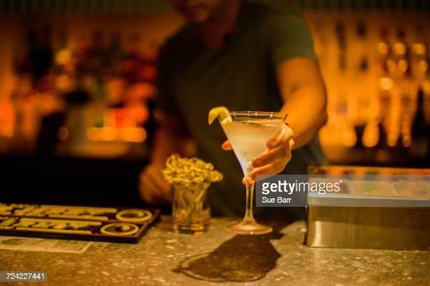 Bar tender serving cocktail drink over bar
