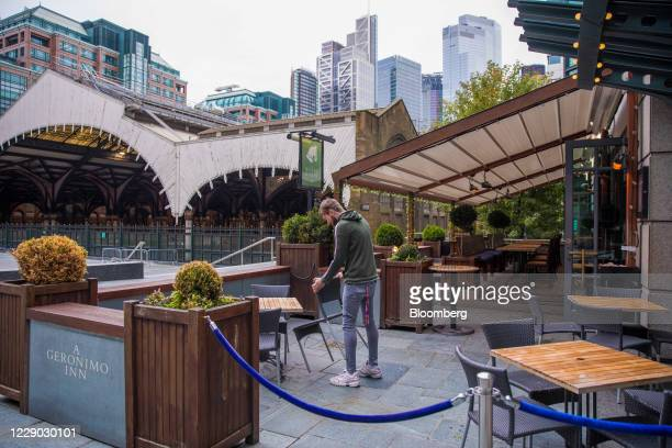 Bar worker sets up table places outside a public house in the City of London, U.K., on Monday, Oct. 12, 2020. The approach of Brexit has London...