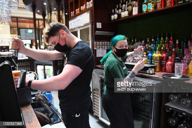 Bar workers prepare customers' drinks orders at a re-opened Wetherspoons pub in Glasgow on April 26, 2021 following the relaxing of some Covid-19...