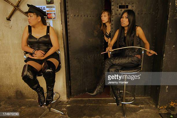 M bar workers try to attract passers by in Bangkok's red light district of Patpong