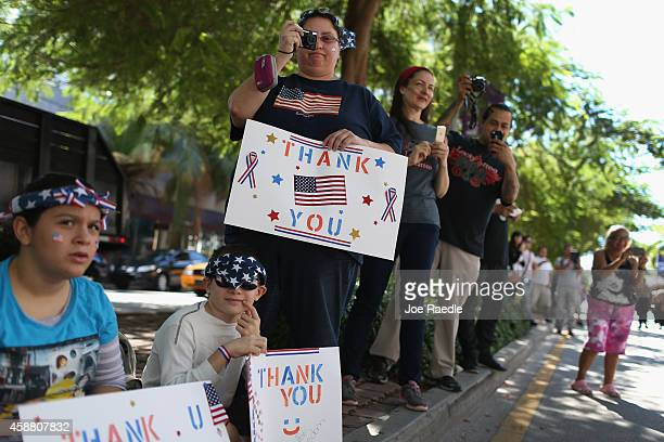 Barabara Rodriguez holds a sign that reads Thank you as she watches the parade march past during the Miami Beach Veterans Day Ceremony on November 11...