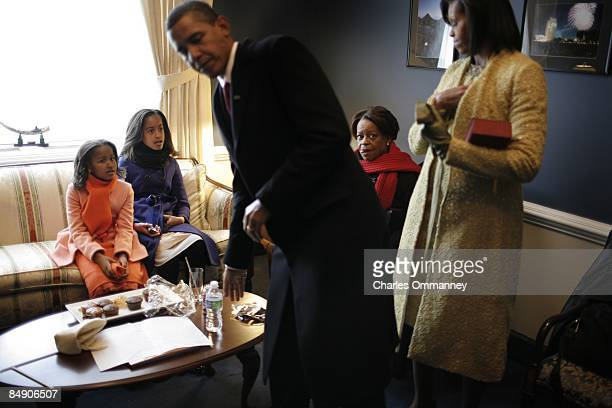 Barack H. Obama, his wife Michelle and daughters Malia and Sasha hold in a small room in the Capital before he is sworn in by Chief Justice John...