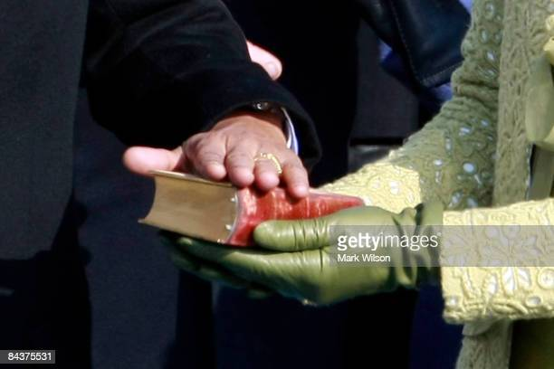 Barack H Obama places his hand on the Abraham Lincoln bible as he is sworn in by Chief Justice John Roberts as the 44th president of the United...