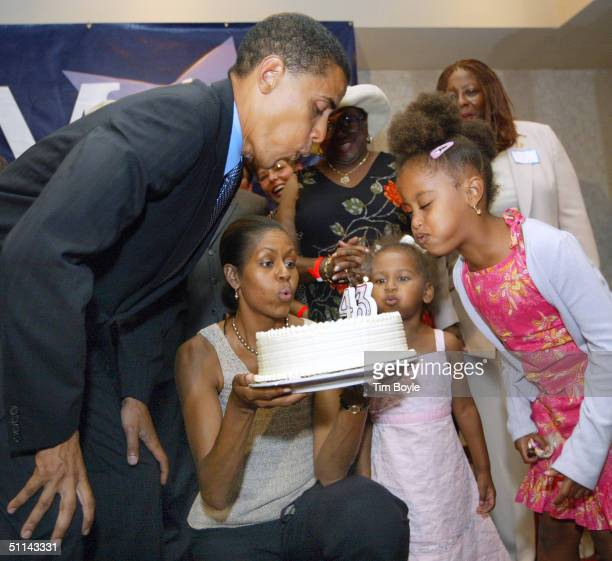 Barack Obama blows out candles on his birthday cake at his 43rd birthday celebration with his wife Michelle who is holding the cake and daughters...