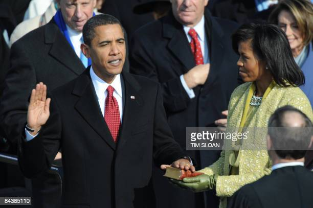 Barack Obama is sworn in as 44th US president by Chief Justice John Roberts beside wife Michelle on January 20 2009 at the Capitol in Washington DC...