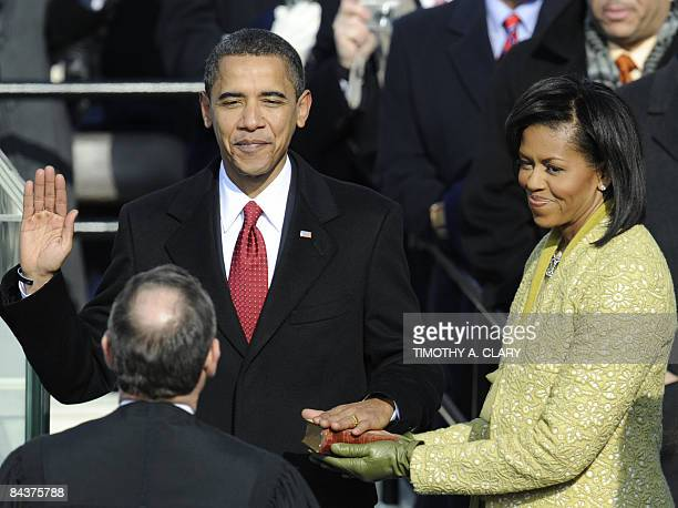 Barack Obama is sworn in as the 44th US president by Supreme Court Chief Justice John Roberts as his wife Michelle holds the Bible in front of the...