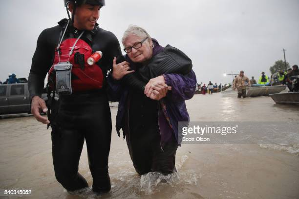 Barb Davis 74 is helped to dry land after being rescued from her flooded neighborhood after it was inundated with rain water remnants of Hurricane...